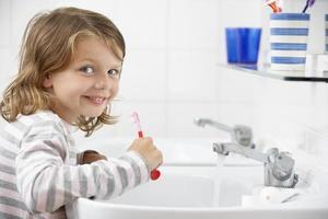 menina no banheiro escovando os dentes foto