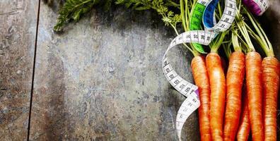 fita de medição de cenouras frescas foto