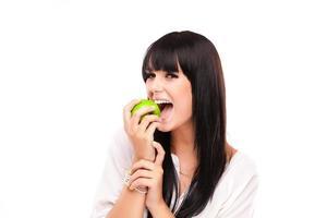 linda mulher morena com maçã verde sobre fundo branco foto