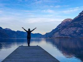 silhueta de mulher no cais à beira do lago foto