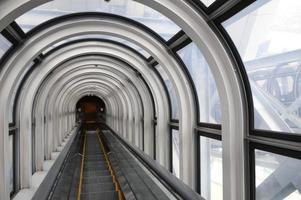 escada em movimento em um túnel de vidro foto