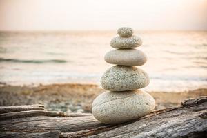 monte de pedras inukshuk na madeira lançada à costa na praia foto