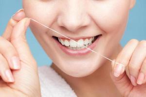 garota limpando os dentes com fio dental. cuidados de saúde foto