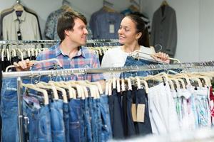 casal comprando jeans azul na loja foto