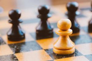peões de xadrez branco e preto em pé no tabuleiro de xadrez foto