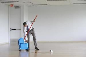 empresário usando esfregão no quarto vazio foto