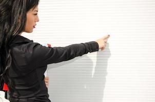 mulher mostra uma parede em branco foto