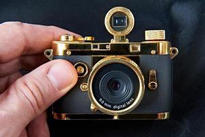 mini câmera dourada de presente na mão grande