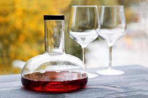 jarra de vinho e copos vazios foto
