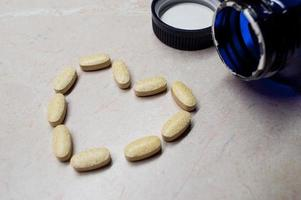 pílulas / comprimidos de vitaminas e minerais em forma de coração / vista lateral para o símbolo foto
