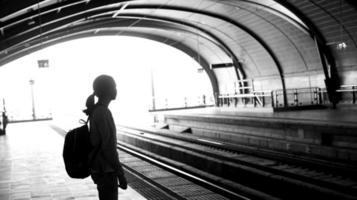 mochileiro de garota turista silhueta esperando o trem no foto