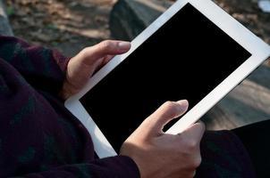 mulher com tablet digital se comunicar no parque foto