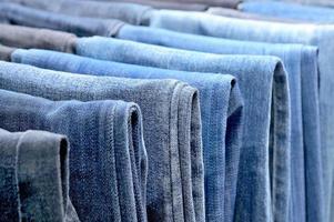 muitos jeans coloridos pendurados em cabides foto