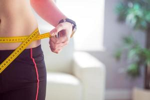 mulher magro, medindo a cintura com fita métrica foto