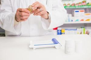 farmacêutico, segurando o frasco de medicamento foto