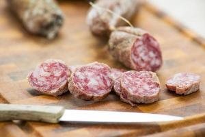 fatias de salame italiano na tábua com faca de cozinha foto