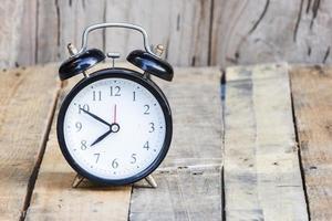despertador no chão de madeira foto