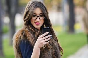 bela garota no parque, olhando para o telefone móvel foto