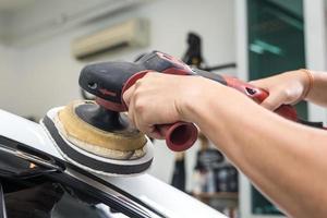 polimento de carro série: trabalhador encerando carro branco foto