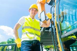 construtor asiático com escavadeira no canteiro de obras foto