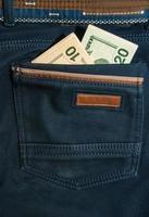 dólares americanos no bolso de trás da calça jeans foto