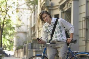 empresário com telefone celular sentado na bicicleta