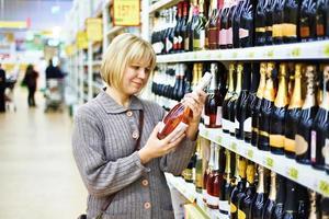 mulher escolhendo vinho rosa foto