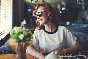 jovem mulher bonita descansando na loja de café depois de andar