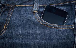 smartphone preto no bolso da calça jeans. fundo. foto