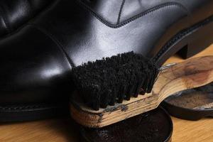 sapatos clássicos de couro preto com creme de polimento e pincel