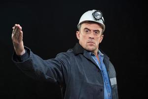 homem com chapéu de mineiro de carvão e dedo de pontos de roupas de segurança