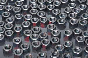 porcas de metal brilhantes sobre uma superfície de metal
