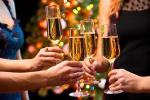 mãos femininas com copos de cristal de champanhe