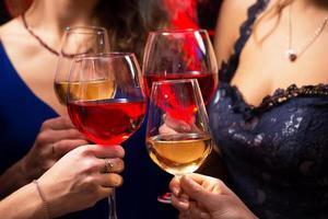 mãos femininas com taças de cristal de vinho