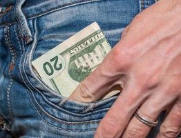 mão masculina com dólares no bolso foto