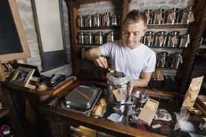 vendedor, colher o chá do recipiente na loja foto
