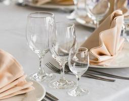 servido com um prato e copos em cima da mesa foto