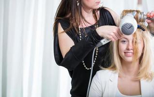 cabeleireiro / penteado trabalhando no cabelo de uma jovem mulher
