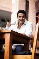 homem segurando um café e sorrindo foto