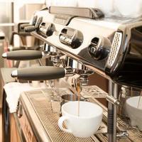 grande máquina de café expresso em uma cafeteria com uma caneca branca foto