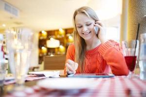 mulher no café com touchpad e telefone foto