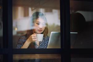 mulher asiática beber café e trabalhando no laptop no café foto
