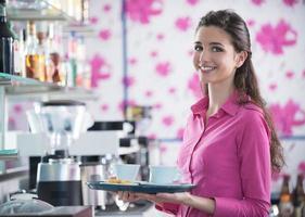 jovem garçonete sorridente, servindo café no bar foto