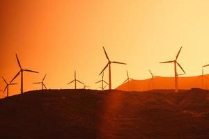 turbinas eólicas elétricas fazenda silhuetas no fundo do sol