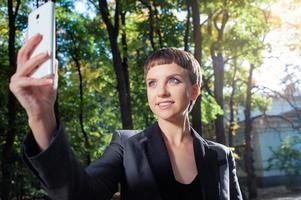 mulher atraente em trajes formais tirando foto com seu telefone inteligente
