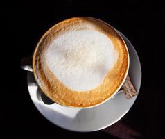 xícara de café na mesa escura foto