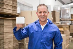 trabalhador de armazém sorridente segurando caixa pequena foto