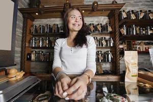 jovem proprietária olhando para longe na loja de chá foto