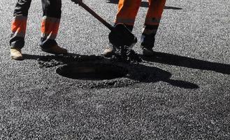 asfalto em andamento, trabalhadores com uma pá foto