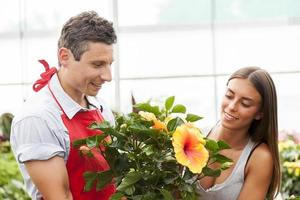 vendedor sorridente vende uma planta para um cliente bonito foto